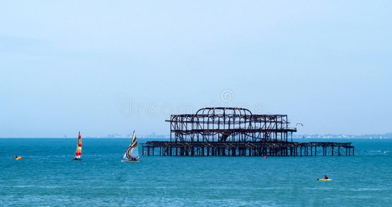 Sailing boats around the derelict West pier in Brighton stock images