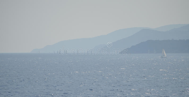 Sailing boats in the mist of blue shades of coasts of the Elba Island. royalty free stock photography