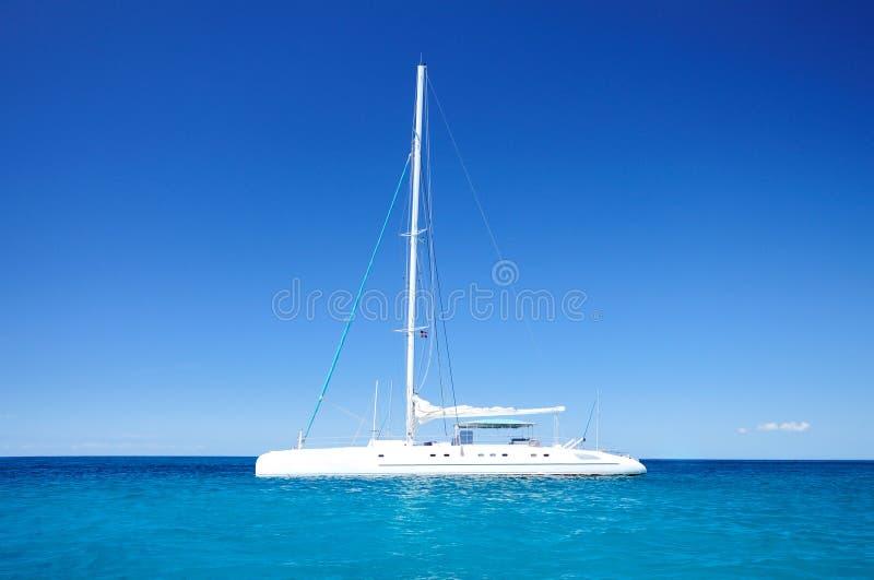 Sailing catamaran in the blue carribean sea royalty free stock photos
