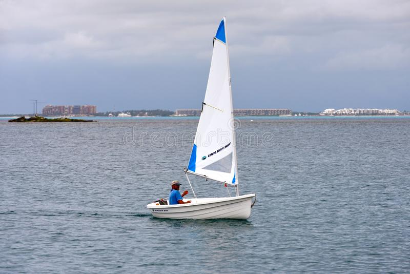 Sailing dinghy. Happy cruiser going ashore from his boat in anchorage with sailing tender, rigid plastic dinghy Walker Bay. Mexico. Isla Mujeres royalty free stock images