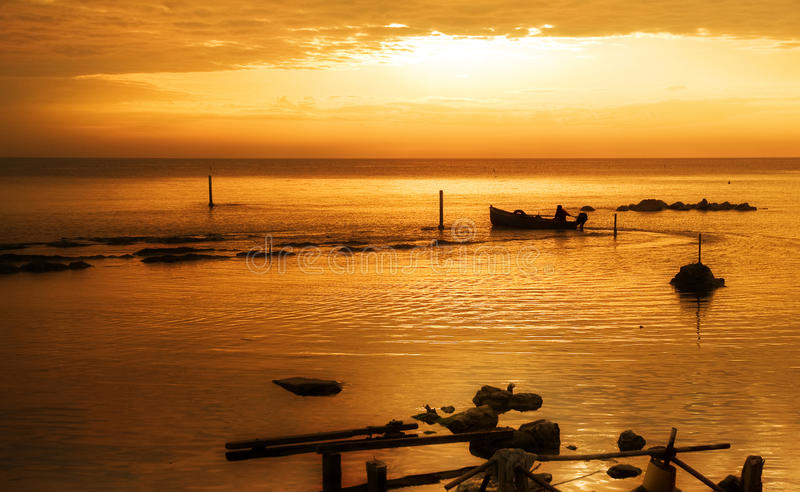 Sailing into golden sea. Boat into the sea with a golden light in the morning