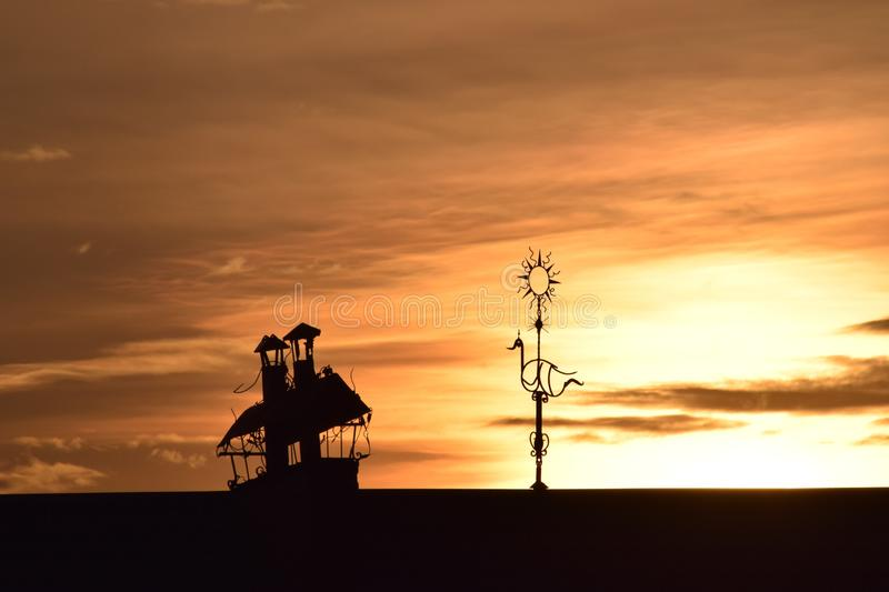 Sailing home. A fantasy steampunk ship under the sky of fire sunset. Usually it is just a pipes and wind vane on the roof. But sun magic, shadows and right point royalty free stock photo