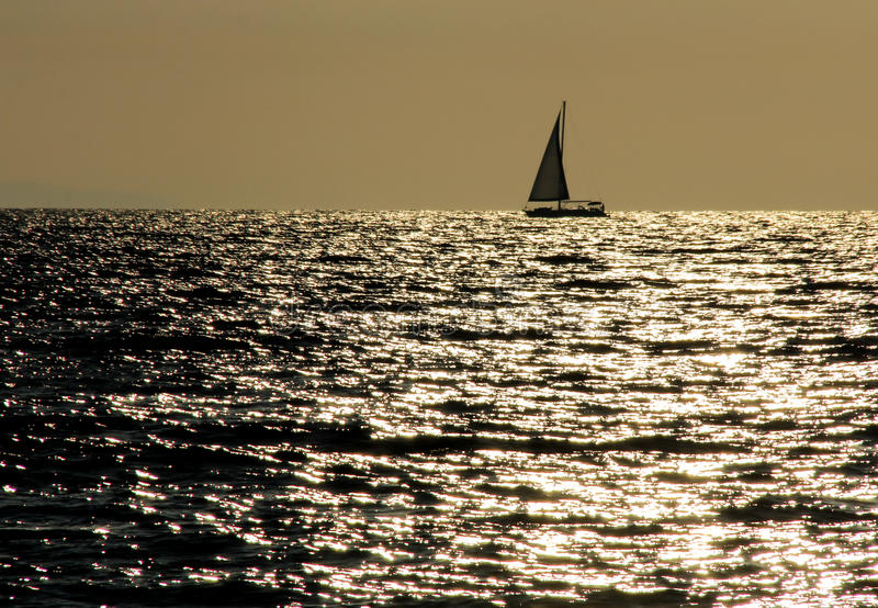 Sailing. Luminous sea with sailboat. Shimmer painted on water royalty free stock photos