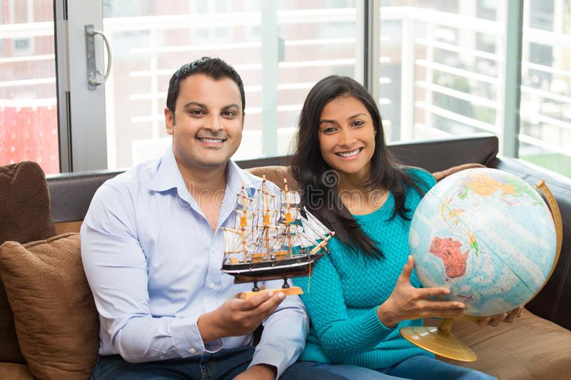 Sailing the ocean blue. Closeup portrait, young couple holding ship and map globe, showing excitement to travel the world, isolated indoors home background stock image