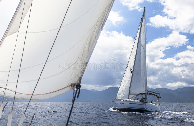 Sailing. Racing yacht in the Mediterranean sea on the background of a stormy sky. Luxury Lifestyle royalty free stock image