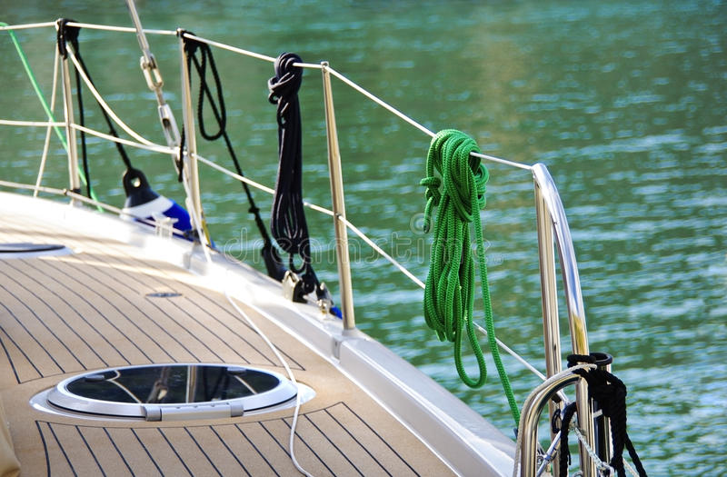 Sailing rigging. Sailing boat detail on sea water background. Ropes and knots of sailboat. Tackles on the rigging yacht. Wooden deck of yacht and bond of ropes royalty free stock images