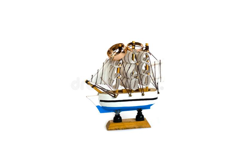 Sailing ship model with wedding rings isolated on white background royalty free stock photography