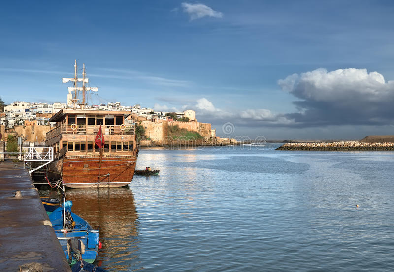 Sailing ship near the pier and the boat (even with the fishermen) on the background of the old fortress and buildings made of whit stock photography