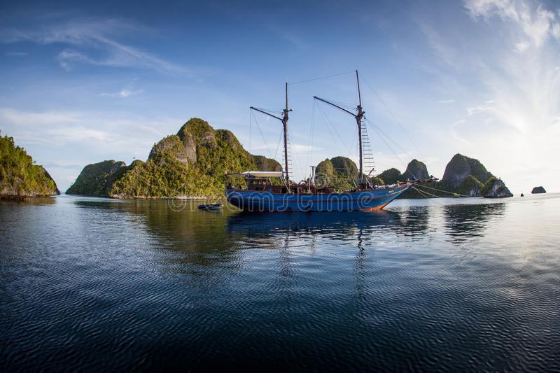 Sailing Ship and Tropical Islands in Wayag, Raja Ampat. A Pinisi schooner floats in a beautiful lagoon surrounded by limestone islands in Raja Ampat, Indonesia stock photo