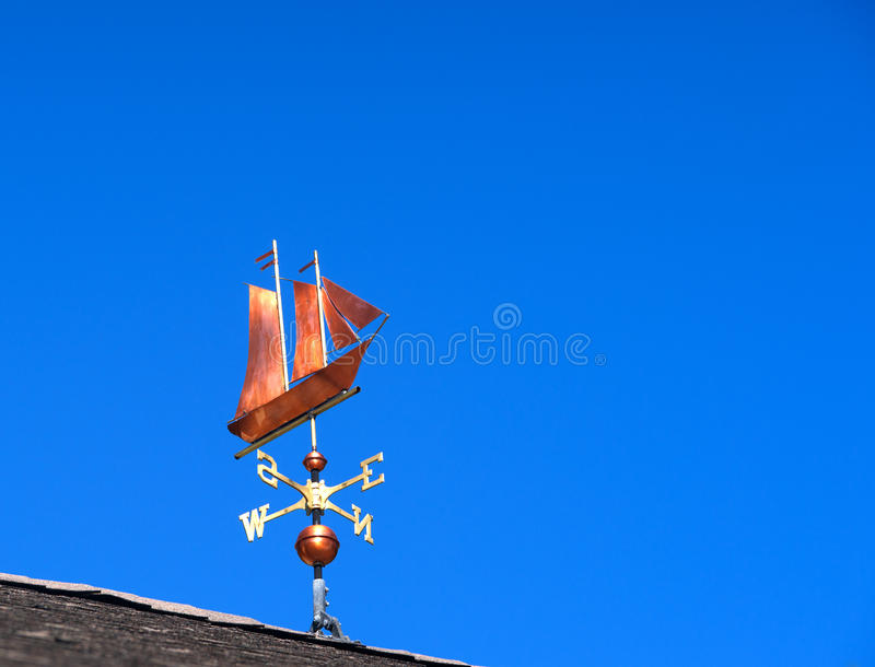 Sailing ship weather vane. A copper weather vane at the peak of a roof with blue sky in the background royalty free stock images