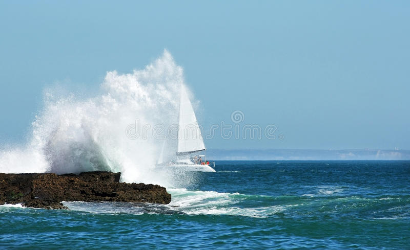 Sailing in the storm through the big wave stock image