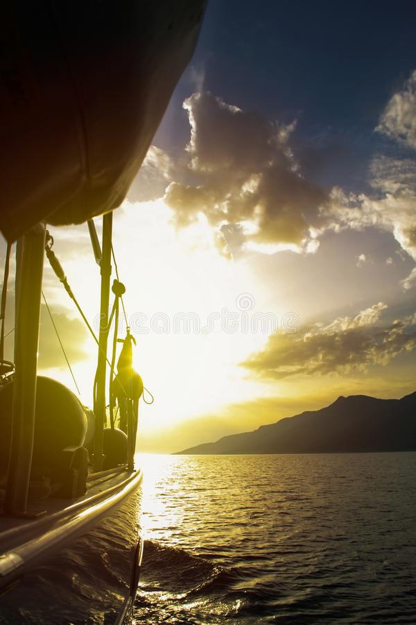 Sailing to sunset with sailing boat stock image