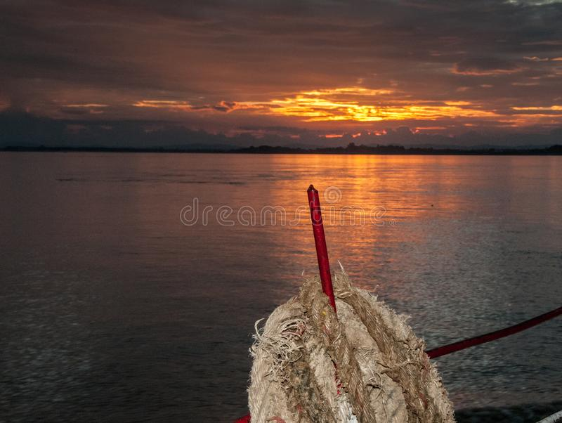 Sailing towards Bagan on the Irrawaddy River. A beautiful warm sunset is reflected in the waters of the great Burmese river royalty free stock photos