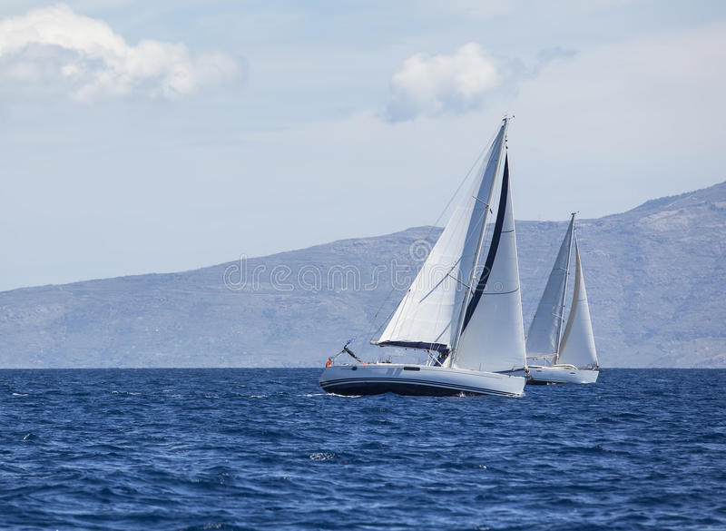 Sailing in the wind through the waves at the Aegean Sea in Greece. Luxury yachts. royalty free stock image