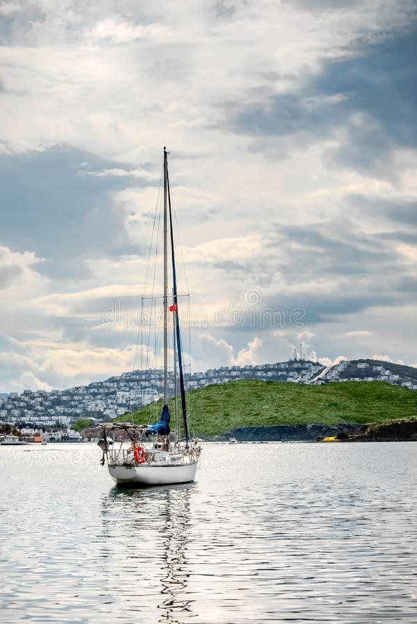 Sailing yacht anchored in Gumusluk bay, Bodrum, Turkey. On a cloudy winter day stock photography