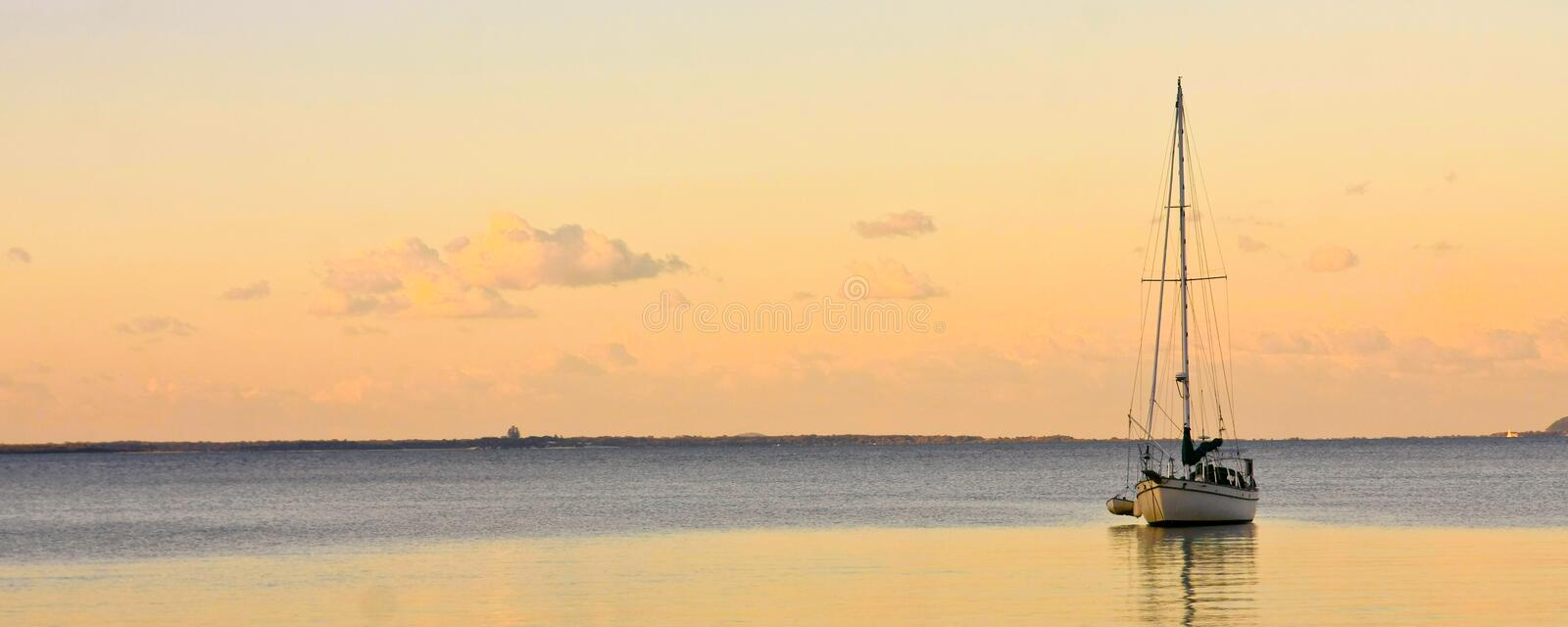 Sailing yacht on calm sea at sunset royalty free stock photography