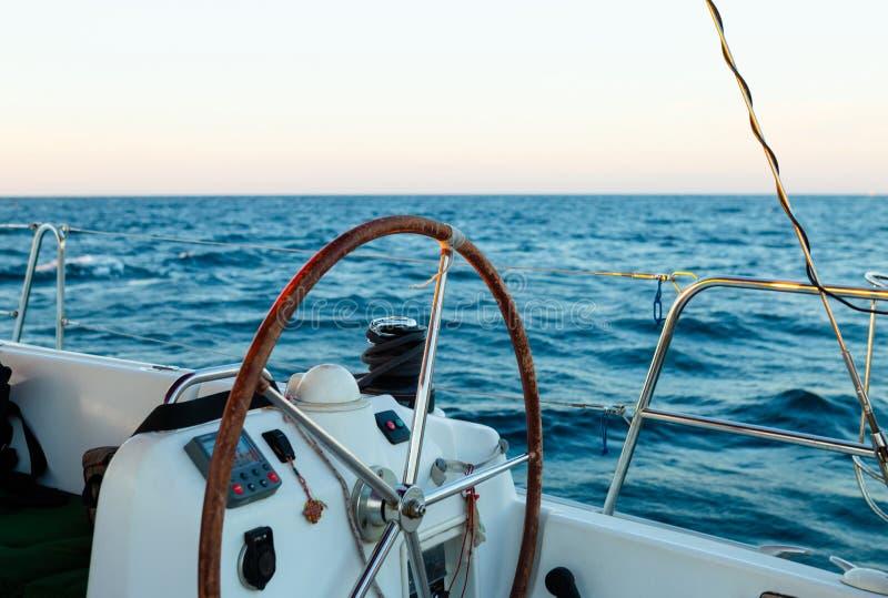 Sailing yacht control wheel, blue sea on background royalty free stock photos