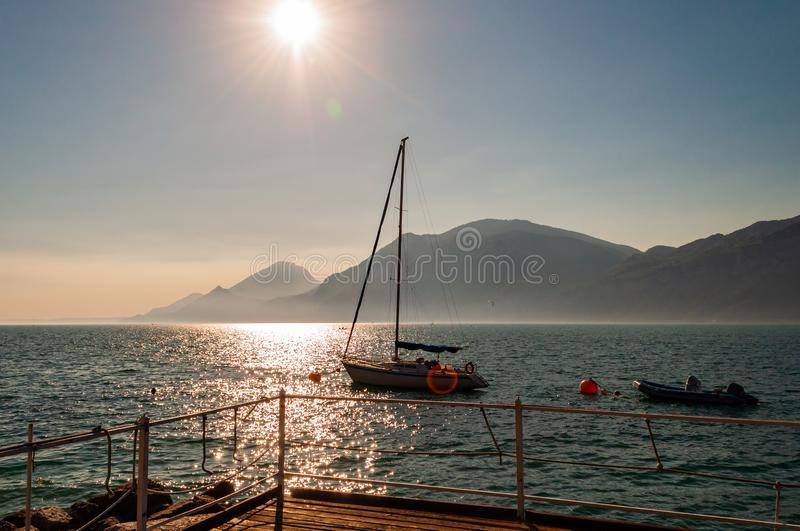 Sailing yacht floating near the pier on misty Garda lake with high dolomite mountains with sun shining above in the sky on the. Background royalty free stock image