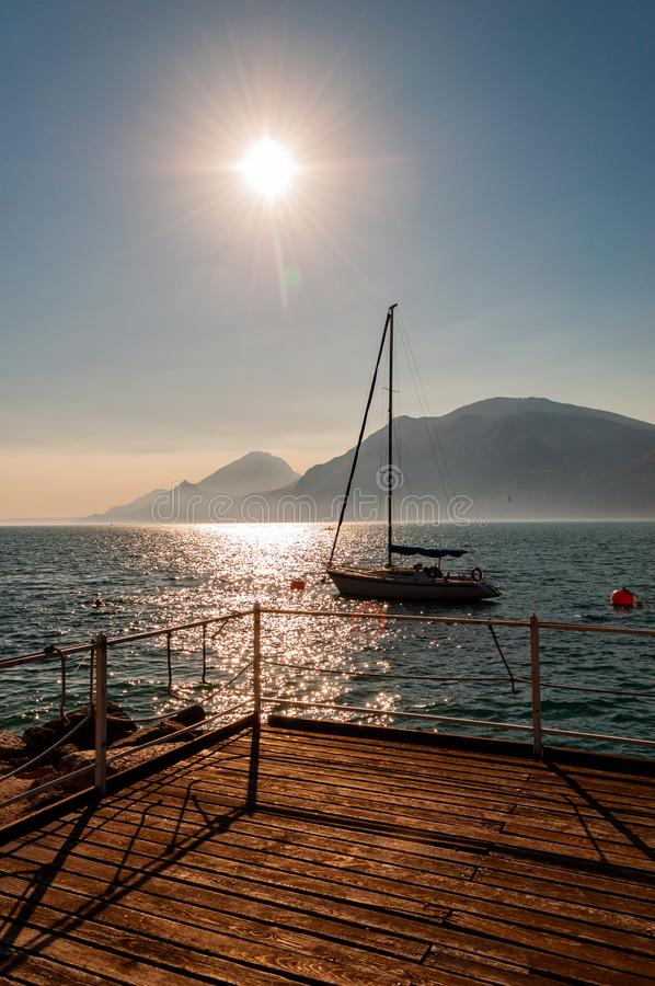 Sailing yacht floating near the pier on misty Garda lake with high dolomite mountains with sun shining above in the sky on the. Background stock image
