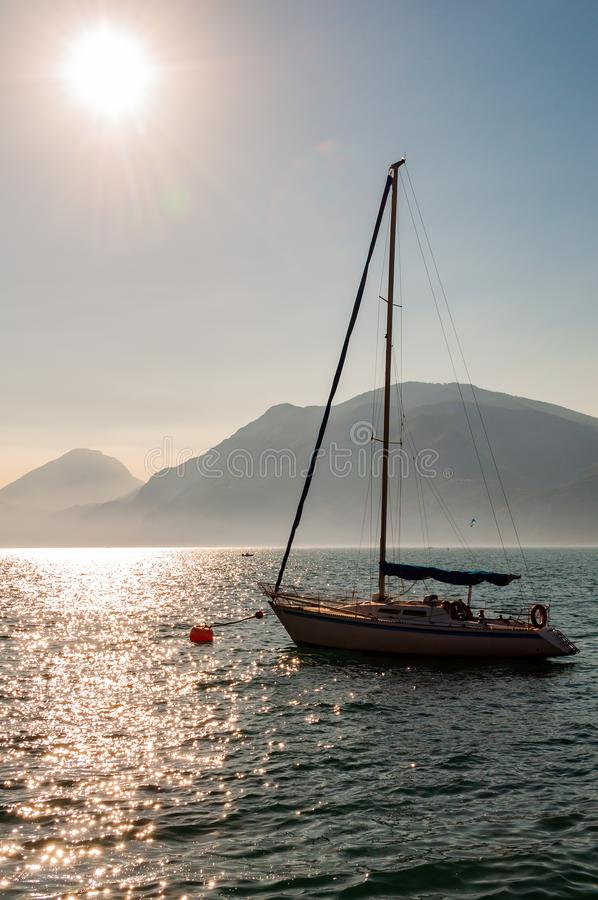 Sailing yacht floating near shore of misty Garda lake with high dolomite mountains with sun shining above in the sky on the. Background royalty free stock photo