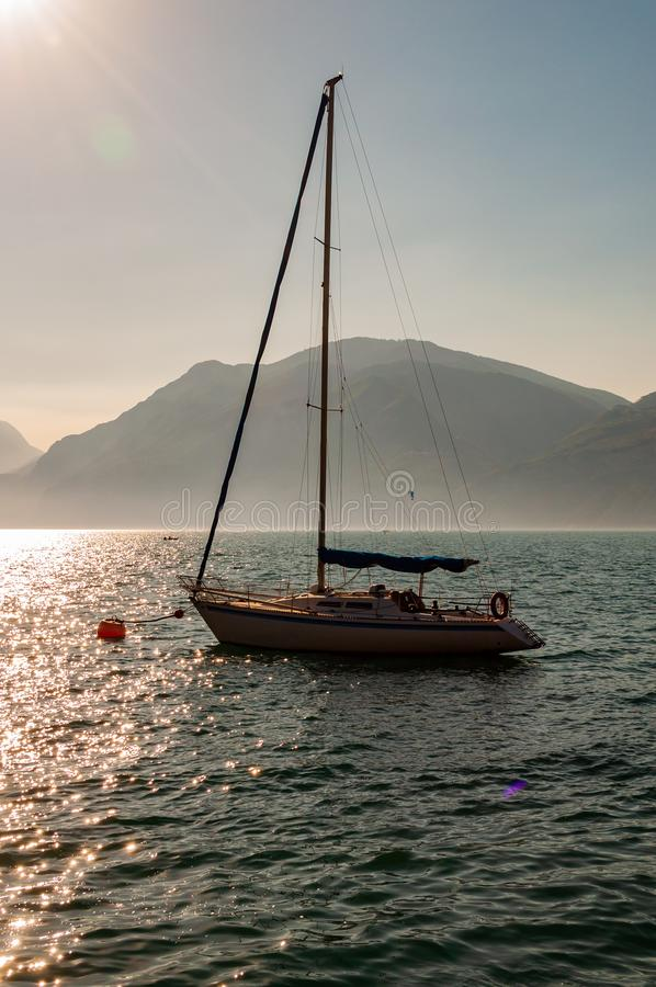 Sailing yacht floating near shore of misty Garda lake with high dolomite mountains with sun shining above in the sky on the. Background royalty free stock photos