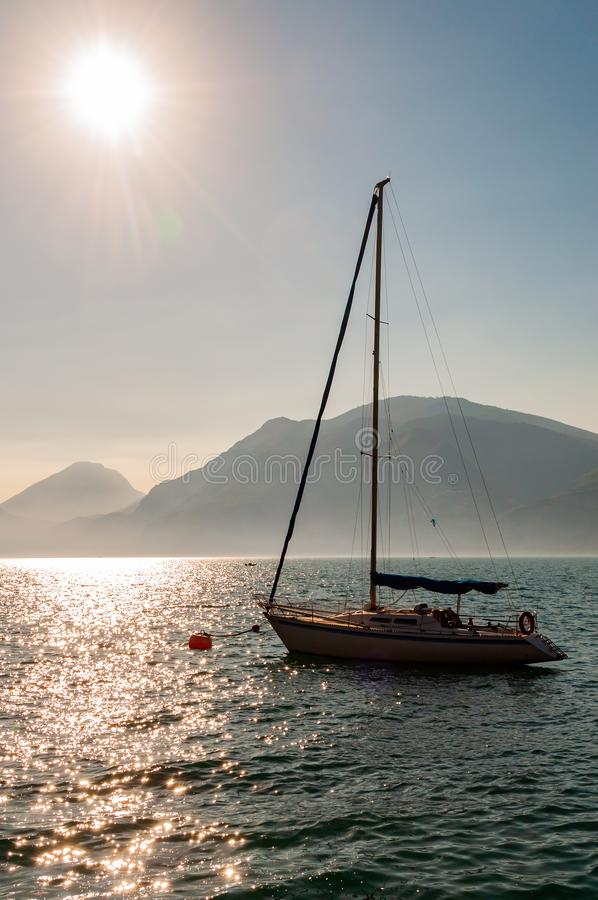 Sailing yacht floating near shore of misty Garda lake with high dolomite mountains with sun shining above in the sky on the. Background royalty free stock photography