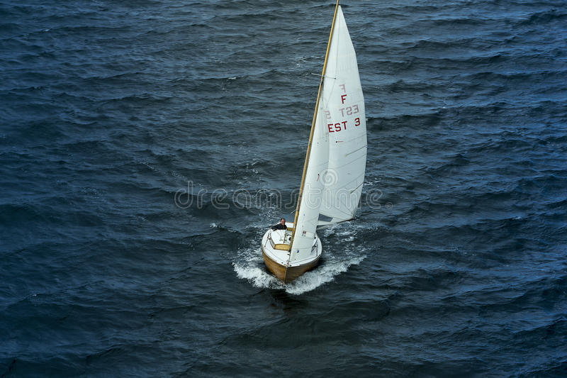 Sailing yacht goes to sea. Small sailing yacht goes to open sea stock photo
