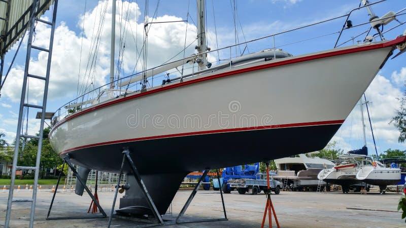 Sailing yacht on hardstand in Phuket boat lagoon marina for antifouling royalty free stock photo