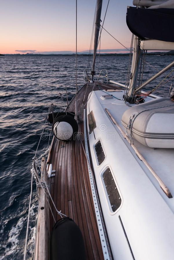 A sailing yacht sailing on the blue sea during sunset stock image