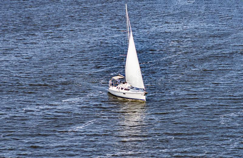 Sailing yacht sailing with an open white sail. Sports and recreation royalty free stock image