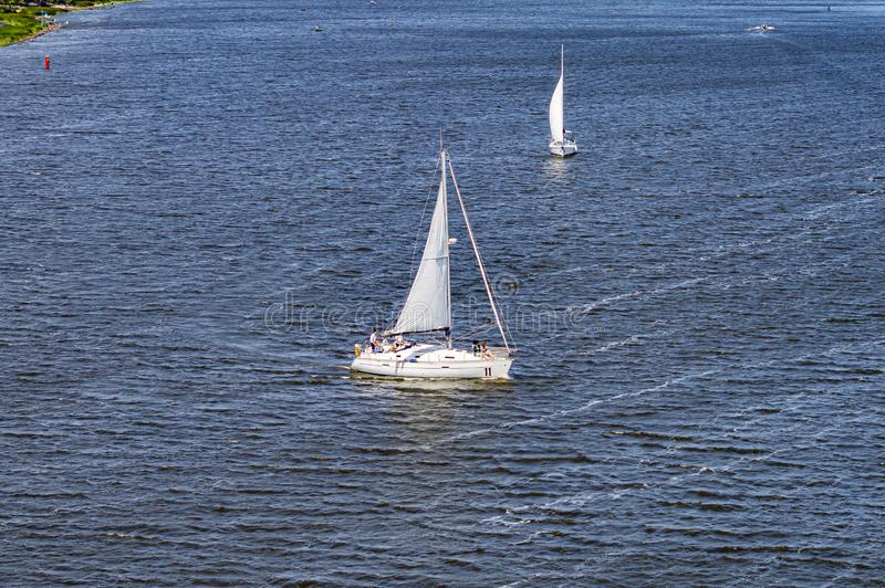 Sailing yacht sailing with an open white sail. Sports and recreation royalty free stock photography