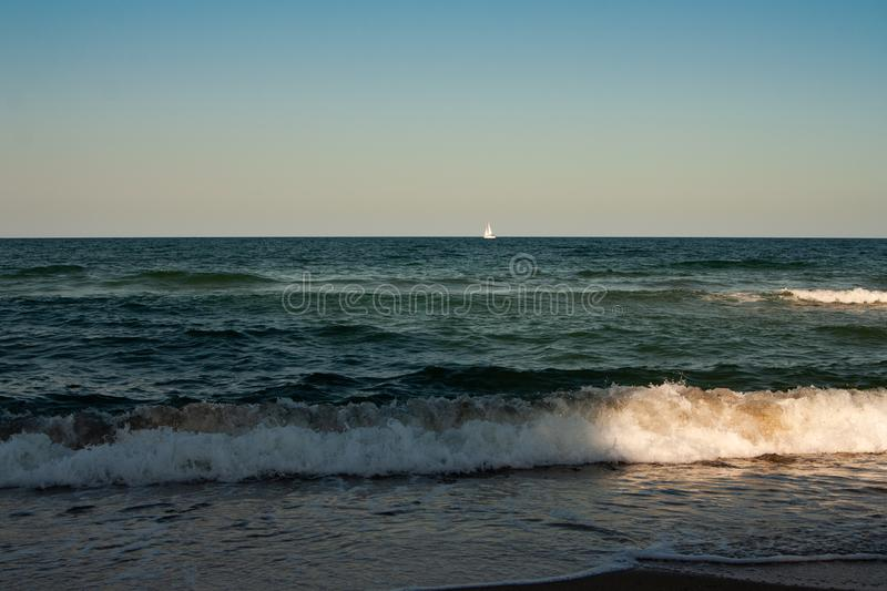 Sailing yacht with white sails in the open Sea. royalty free stock photo