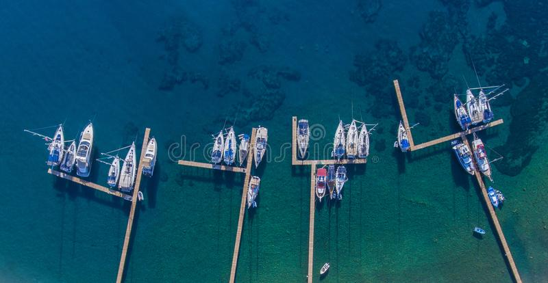 Sailing yachts and boats moored to the wooden piers. stock photos