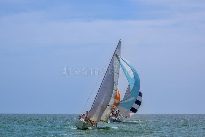 Sailing Yachts in the Open Sea. Sunny weather in the open sea. Three sailing yachts with spinnakers going with a significant tilt stock images