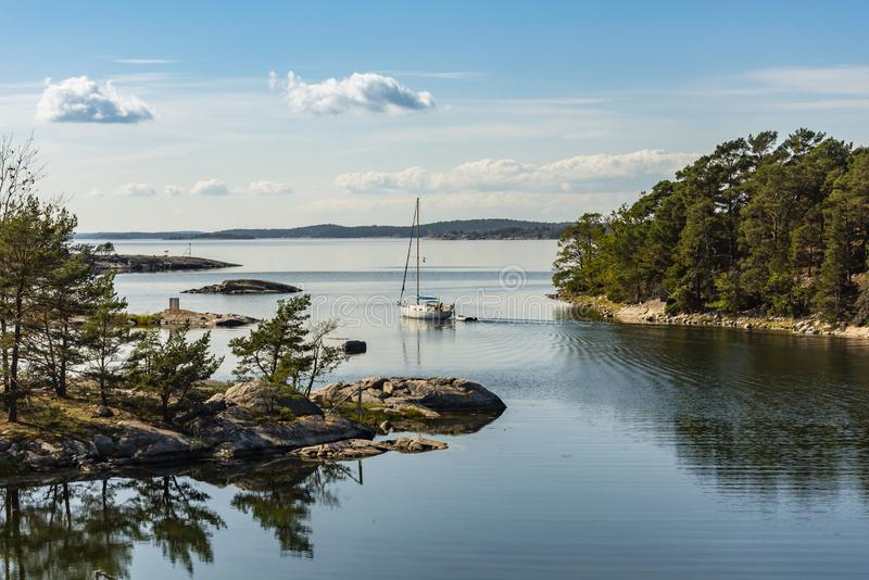 Sailingboat navigating through narrow passage Stockholm archipelago. Sailingboat navigating through the narrow passage from Jungfruskär nature reserve in stock photography