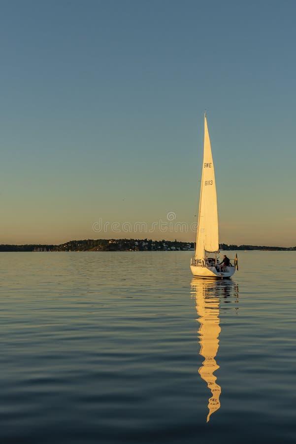 Sailingboat som driver den döda lugna soliga aftonStockholm skärgården royaltyfri foto