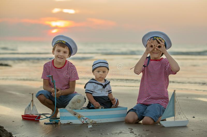 Sailor baby boy, cute child, playing on the beach with wooden bo royalty free stock images
