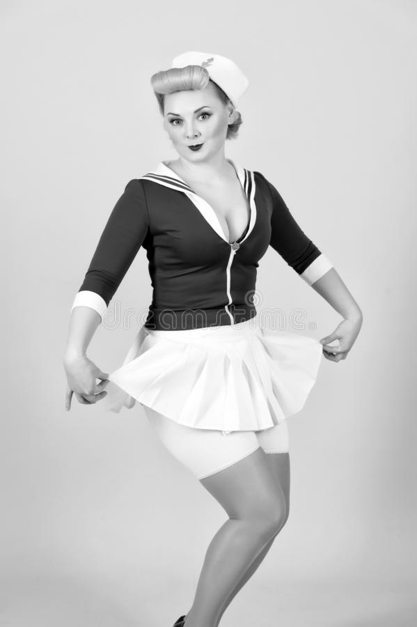 Sailor girl in pin-up style with white skirt. Vintage styled blonde woman isolated on gray background royalty free stock image