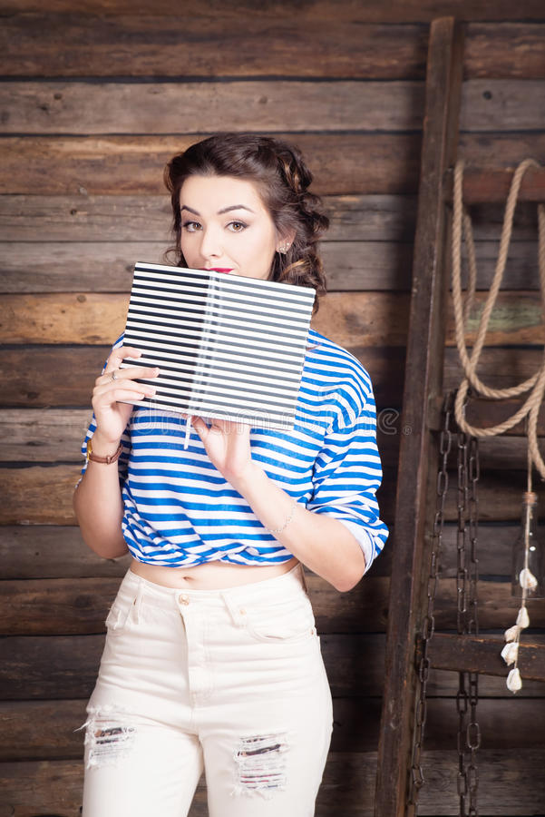 Sailor girl with striped copybook and sailor`s striped vest royalty free stock photo