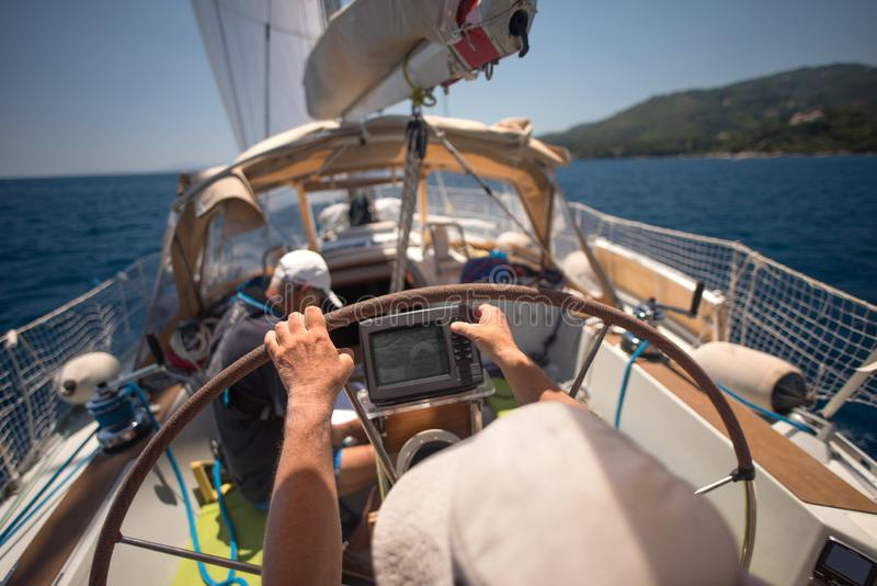 Sailor holding the helm of the sailboat royalty free stock image