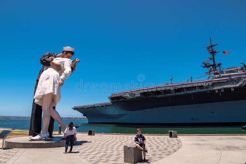 Sailor Kissing Nurse statue beside USS Midway aircraft carrier museum at the San Diego Harbor California. The USS midway is a retired aircraft carrier that stock photography