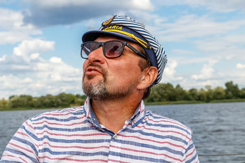 Sailor man in a cap on a boat under sail against the sky and water stock photography