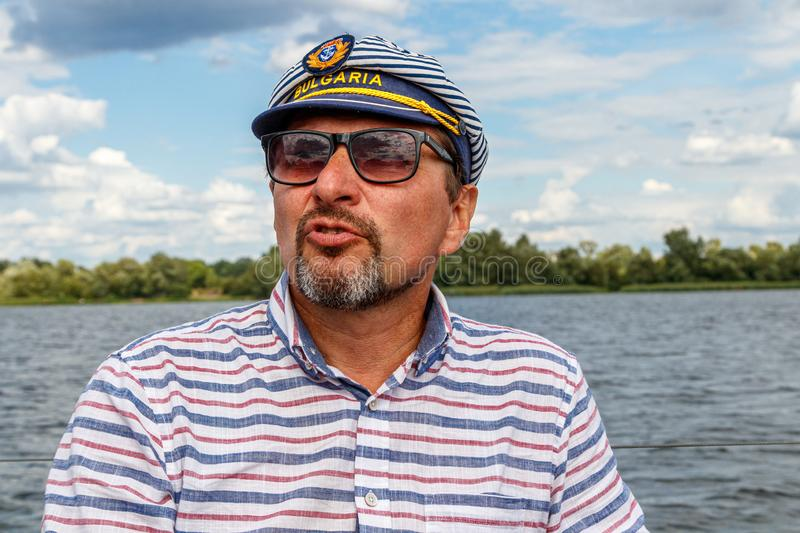 Sailor man in a cap on a boat under sail against the sky and water stock photos