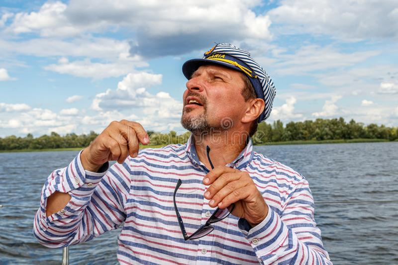 Sailor man in a cap on a boat under sail against the sky and water stock images