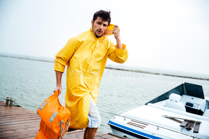 Sailor man in yellow cloak walking at the sea pier. Young handsome sailor man in yellow cloak walking at the sea pier holding life vest stock image