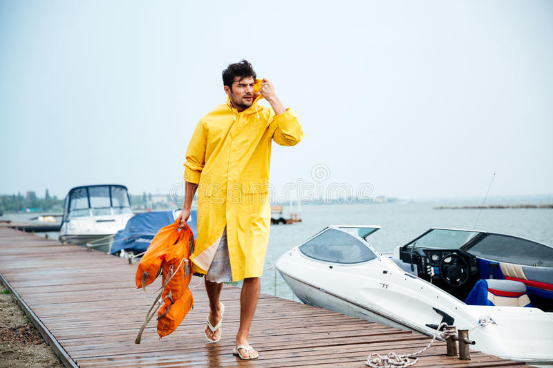 Sailor man in yellow cloak walking at the sea pier. Young handsome sailor man in yellow cloak walking at the sea pier holding life vest royalty free stock photography
