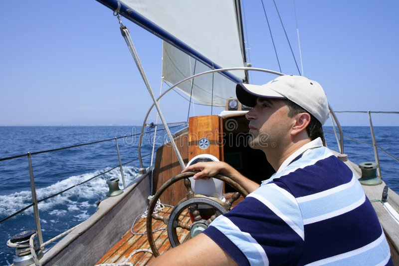 Sailor sailing in the sea. Sailboat over blue stock photos