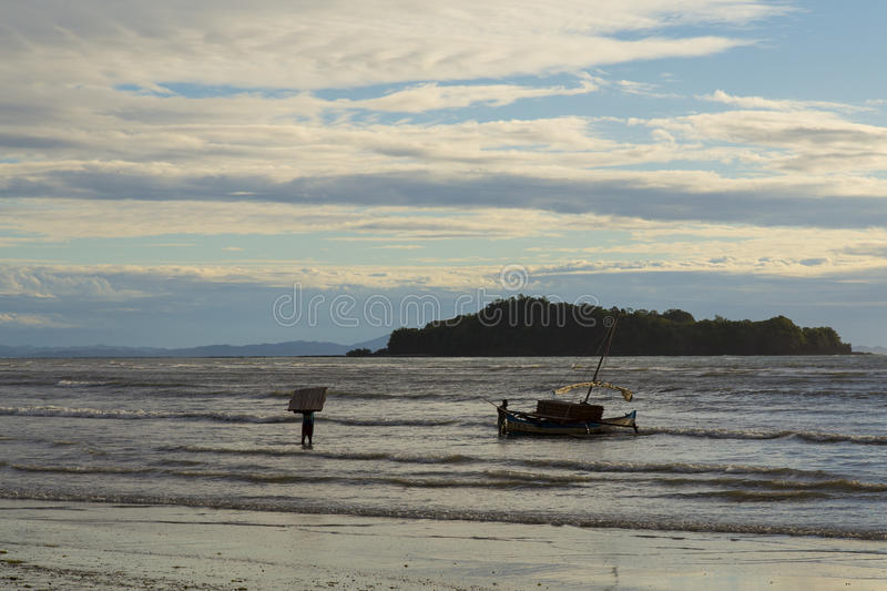 Sailor stranding a boat on a low tide Sea in the sunset royalty free stock images
