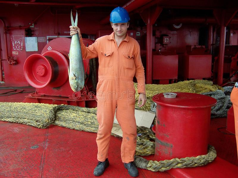 Sailor in uniform shows his lucky catch - big fish caught in ocean from ship deck of oil tanker royalty free stock photo