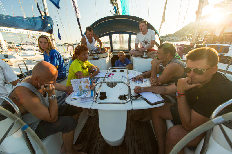 Sailors on skipper's briefing in the yacht wardroom during sailing regatta. PATRAS, GREECE - CIRCA OCT, 2014: Unidentified sailors on skipper's briefing in the royalty free stock image